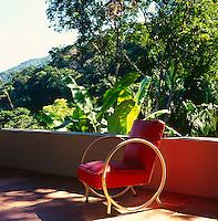 A red chair with a cane frame on this contemporary terrace with the Mexican jungle as a backdrop