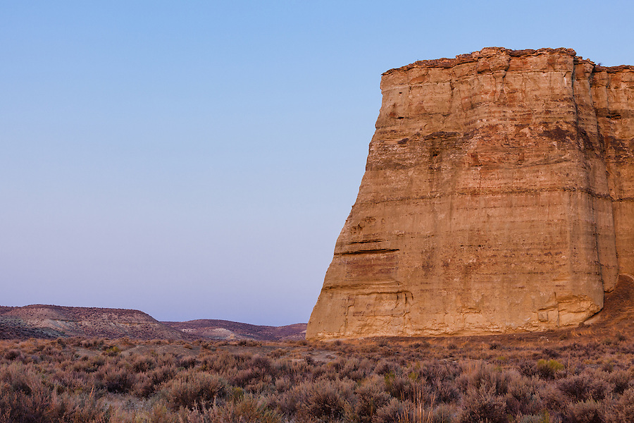 The soft light of dawn bathes one of the sides of the Pillars of Rome and surrounding sagebrush in Southeast Oregon with a purplish gentle pastel light.