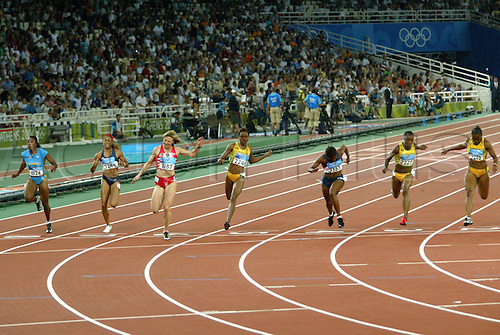 21 August 2004: Belorussian sprinter Yuliya Nesterenko (BLR) (1187) crosses the finish line in a time of 10.93 seconds to win the Women's 100m final held at the Olympic Stadium. Lauryn Williams (USA) (3363) was 2nd and Veronica Campbell (JAM) (2223) was 3rd. 2004 Olympic Games, Athens, Greece. Photo: Action Plus...040821 olympics olympic athletics track and field athlete run running runner runs sprint sprinting sprinter women woman womens.female