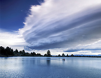Fly fisherman in float tube in small pond with approaching storm. Freemont National Forest, Oregon.