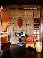 The living room in the beach pavilion is furnished with a colourful daybed and armchair