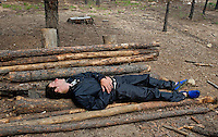Photo story of Philmont Scout Ranch in Cimarron, New Mexico, taken during a Boy Scout Troop backpack trip in the summer of 2013. Photo is part of a comprehensive picture package which shows in-depth photography of a BSA Ventures crew on a trek. In this photo, an exhausted  BSA Venture crew member finds a dry resting spot to grab a quick nap between climbs  at Cimarroncito Camp in the backcountry at Philmont Scout Ranch.  The stacked together logs created a makeshift coach around the fire pit area.<br /> <br /> The  Photo by travel photograph: PatrickschneiderPhoto.com