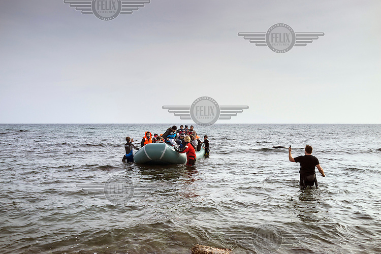 A boat carrying refugees approaches the shoreline of the Greek Island of Lesvos. A man filming for a virtual reality records the boat arriving.