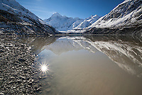 Aoraki Mt Cook reflected in Hooker Lake on a pristine blue sky day. Sunstar & lens flare.