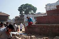 A Nepali woman read newspaper seating on the base of a destroyed temple at Kathmandu Durbar Square, Kathmandu, Nepal. May 03, 2015