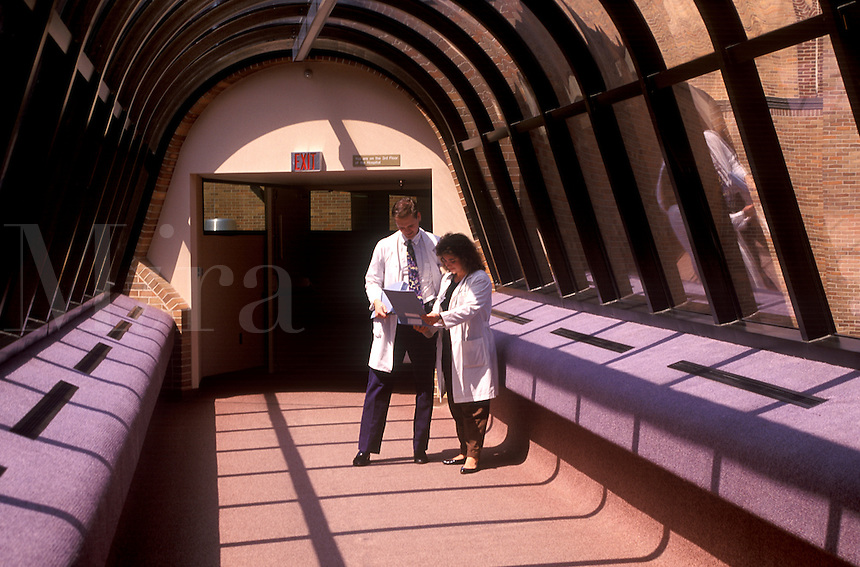 Doctors consult in a hospital hallway.