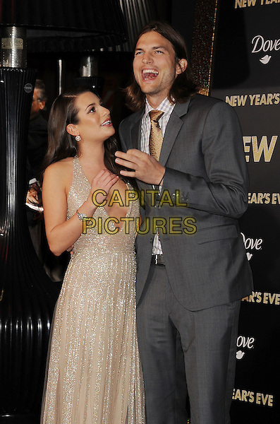 "Lea Michele & Ashton Kutcher.The World Premiere of ""New Year's Eve' held at The Grauman's Chinese Theatre in Hollywood, California, USA..December 5th, 2011.half 3/4 length grey gray suit jacket stubble facial hair check shirt white yellow tie gold beige dress low cut plunging neckline cleavage hand looking up cheek smiling laughing mouth open.CAP/ROT/TM.©Tony Michaels/Roth Stock/Capital Pictures"