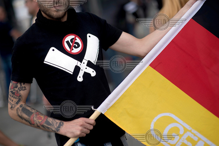 A demonstrator with a German flag and a t-shirt showing an anti-IS symbol at a rally of far right organisations, including the NPD (National Democratic Party of Germany) and the populist PEGIDA movement (Patriotic Europeans Against the Islamisation of the Occident). The demonstration was held inside the government quarter under the slogan 'We For Germany Merkel must go'.