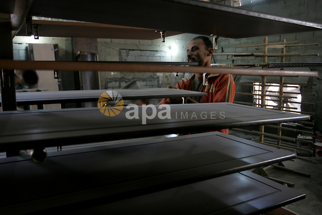 """A Palestinian carpenter works at his workshop for woodwork in Rafah, southern Gaza Strip on November 14, 2011.  An official in the General Federation of Palestinian Industries in Gaza Strip said on Sunday that the Israeli authorities have taken a number of facilities for the Gaza Strip, including furniture exports to the West Bank, and """"Israel"""" and the European markets. Photo by Abed Rahim Khatib"""