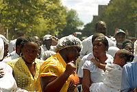 "Several hundred members of the United House of Prayer for All People, a non-denominational Pentecostal church, gather in Harlem in New York on Sunday, August 3, 2008 for a mass baptism. The church, which has held the baptisms on West 115 street since 1937, uses a fire hose to spray the congregation with city water blessed by the church's bishop. The ceremony is accompanied by music played by several brass ""shout"" bands. (© Richard B. Levine)"