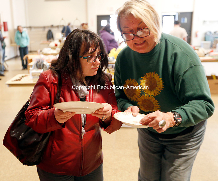 Torrington, CT- 11 April 2015-041115CM07-  Candace Craig, left, of Torrington and Hellen Sellei of New Hartford  look at dishes during a tag sale at the Coe Memorial Park Civic Center in Torrington on Saturday.  The event will help benefit the city's fireworks fund.  The Sullivan Senior Center also held an Antique's Appraisal and tag sale on Saturday.   Christopher Massa Republican-American
