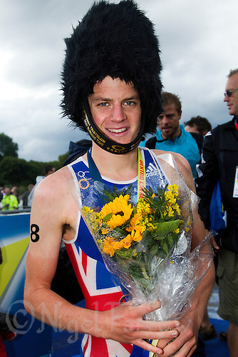 07 AUG 2011 - LONDON, GBR - Jonathan Brownlee (GBR) poses for pictures in the trophy for the fastest run split during the men's round of triathlon's ITU World Championship Series, a bearskin hat .(PHOTO (C) NIGEL FARROW)