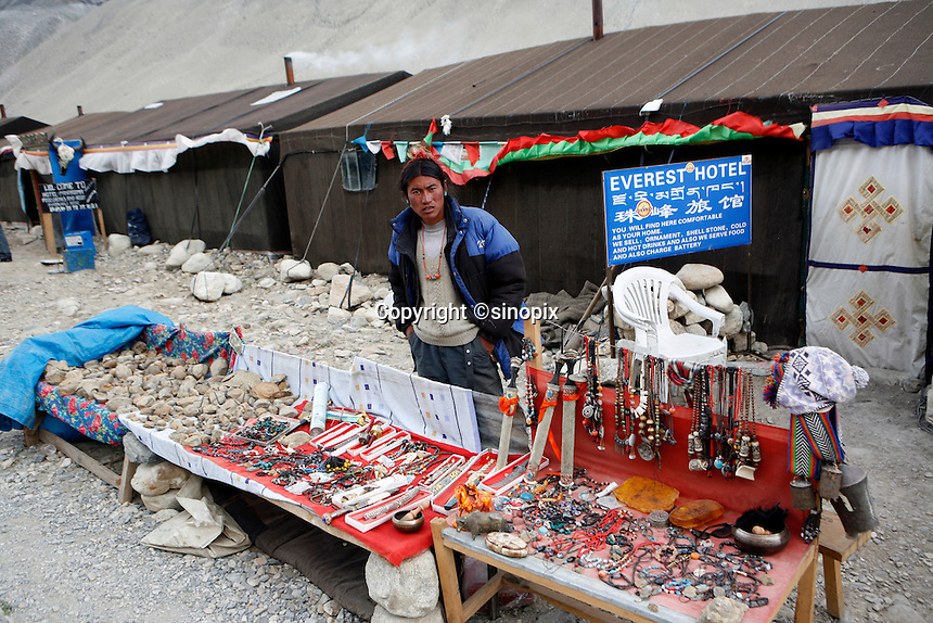 """China started building a controversial 67-mile """"paved highway fenced with undulating guardrails"""" to Mount Qomolangma, known in the west as Mount Everest, to help facilitate next year's Olympic Games torch relay./// A tent owner stands in front his tent guest house selling souvenirs at the tent village near Everest base camp.<br /> Tibet, China<br /> July, 2007"""