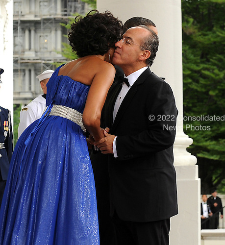 First Lady Michelle Obama embraces Mexican President Felipe Calderon as she and United States President Barack Obama welcome Calderon and Mexican First Lady Margarita Zavala on the North Portico of the White House for a State Dinner in Washington on Wednesday, May 19, 2010.   .Credit: Roger L. Wollenberg - Pool via CNP