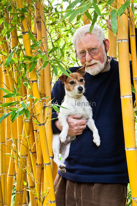 France, Alpes-Maritimes (06), Menton, le Clos du Peyronnet : .William Waterfield dans ses bambous (Phyllostachys) avec son chien Prickle Mention obligatoire du nom du jardin & utilisation presse et livre uniquement, accord préalable pour autre usage // France, Alpes-Maritimes, Menton, le Clos du Peyronnet : William Waterfield in the bamboo (Phyllostachys) with his dog Prickle. Obligatory mention of the garden's name. Only use for press and books, other use require the prior agrees of the owner.