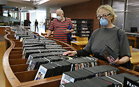 Leland Anderson (left) and Lynn Bennett browse the digital video disc catalog Monday, May 18, 2020, at the Fayetteville Public Library.  The library opened with limited hours and social distancing restrictions for the first time since mid-March because of the covid-19 pandemic. Twenty two patrons visited the library within the first 10 minutes of opening. The library will continue to offer online catalog items for curbside pick-up. Library materials can now be returned in drive-by drop boxes. Check out nwaonline.com/200519Daily/ and nwadg.com/photos for a photo gallery.<br /> (NWA Democrat-Gazette/David Gottschalk)