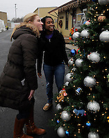 STAFF PHOTO FLIP PUTTHOFF <br /> CHRISTMAS AT THE DEPOT <br /> Donna Graham, left, and Ashlee Malet check the results after helping decorate a Christmas tree on Saturday Dec. 6 2014 outside the Arkansas &amp; Missouri Railroad depot in Springdale. The railroad offered rides with Santa on the A&amp;M passenger train and a Santa Village was set up outside the depot with model train layouts, refreshments and holiday musuc.