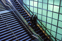 Businessmen on an escalator in Central Tokyo, Japan..04 Dec 2001