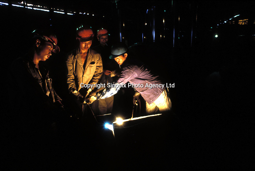 Workers at Guangzhou Shipping and Iron and Steel plant weld in a workshop.  .