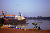 Trombetas bauxite mine, Brazil. Ship loading bauxite, man on bicycle, rainforest on the opposite riverbank.