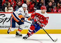 WASHINGTON, DC - JANUARY 31: Lars Eller #20 of the Washington Capitals moves the puck away from Anders Lee #27 of the New York Islanders during a game between New York Islanders and Washington Capitals at Capital One Arena on January 31, 2020 in Washington, DC.