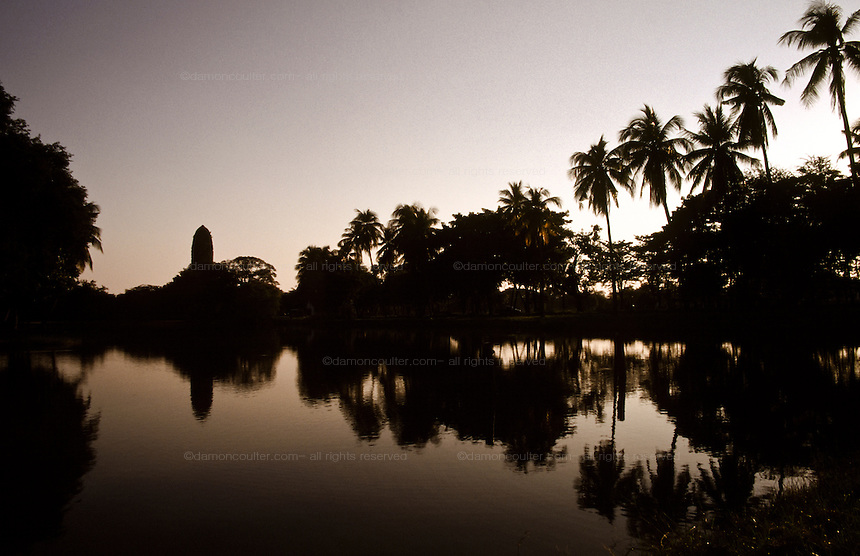 Wat Phra Ram seen in reflection on an ancient pond in the Ayuthaya Historical Park. Thailand.  November 2000
