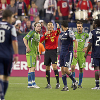 Referee Jorge Gonzalez attempts to settle Seattle Sounders midfielder Erik Friberg (8) and New England Revolution midfielder Monsef Zerka (19). In a Major League Soccer (MLS) match, the Seattle Sounders FC defeated the New England Revolution, 2-1, at Gillette Stadium on October 1, 2011.
