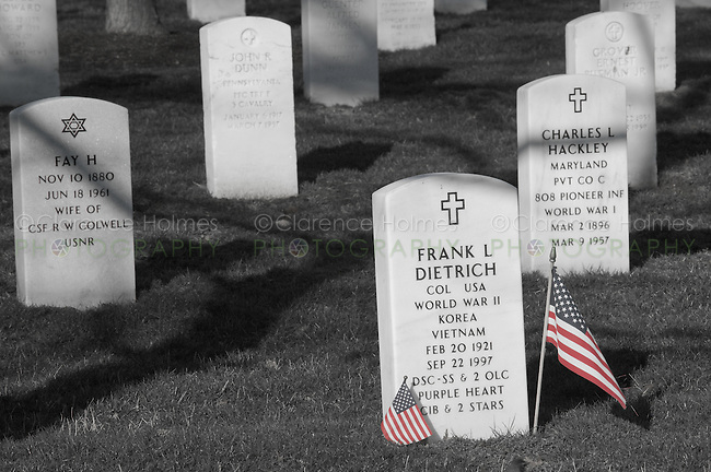 American flags stand next to grave markers in Arlington National Cemetery, Arlington, Virginia