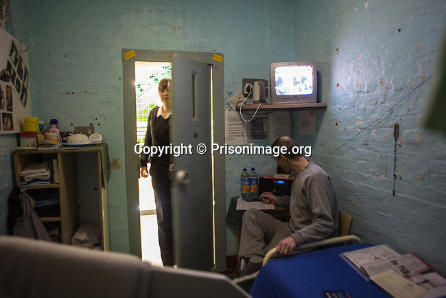 A prisoner sitting at the desk in his cell writing a letter. HMP/YOI Portland, Dorset. A resettlement prison with a capacity for 530 prisoners. <br /> &copy; prisonimage.org.  Any image use must be agreed first. All images must be properly credited.