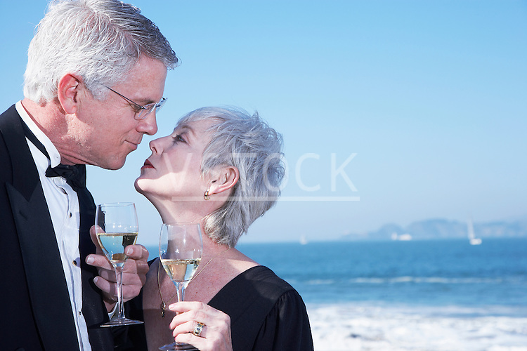 USA, California, Fairfax, Happy mature couple drinking wine and kissing on beach