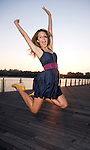 A young blond woman, dressed in a blue sun dress, jumps for joy  on a pier iat dusk