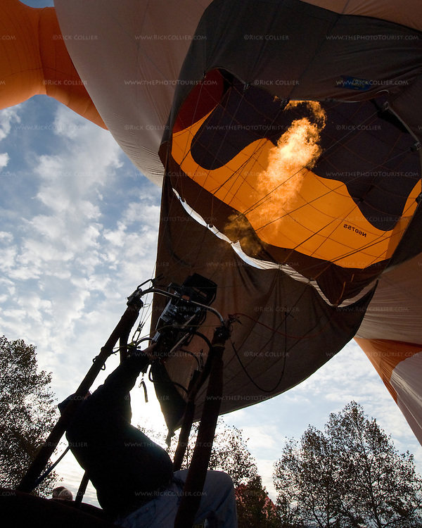 Flames from the gas burner heat the air to fill a hot air balloon.  Balloon Festival, Long Branch Farm, Winchester, Virginia, USA.  © RickCollier.com.