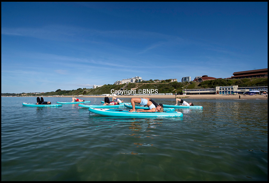 BNPS.co.uk (01202 558833)<br /> Pic: PhilYeomans/BNPS<br /> <br /> Flat Karma...<br /> <br /> Flexible festival goers took to flat-karma seas today for Britain's first ever beach yoga festival.<br /> <br /> Under cloudless blue skies and bright sunshine, 'yogis' on stand up paddle boards took 30 minute classes on the crystal clear sea as Britain finally experienced a break in the wet weather.<br /> <br /> The inaugral three day Beach Yoga Fest is taking place on Bournemouth beach in Dorset involving classes on land and sea over the weekend.