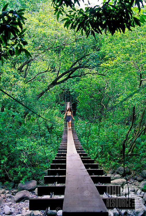 A woman walks on the Chinese swing bridge during a Waiehu Valley hike in the West Maui Mountains.