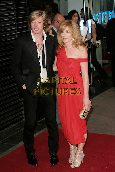 "NICKY CLARKE & KELLY HOPPEN.Arrivals at the ""Sex And The City: The Movie"" World Premiere, Odeon Leicester Square, London, England, UK. .May 12th 2008 .SATC full length red dress black suit gold clutch bag shoes strappy couple .CAP/AH.©Adam Houghton/Capital Pictures."