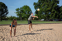 Fit attractive male athlete blocks the serve during a volleyball match at Zilker Park, Austin, Texas.