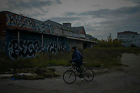 A man rides his bike in a street in front of a abandoned construction in Detroit, the city has more than 16 months of filing for bankruptcy.  10.24.2014. Teddy Blackburn /VIEWpress