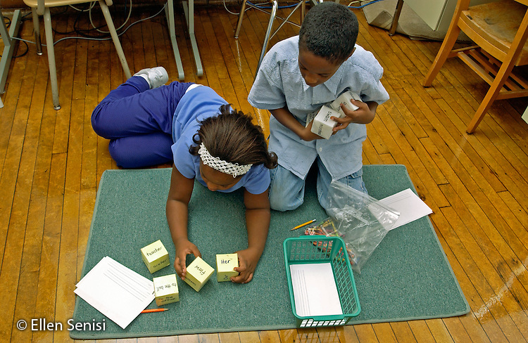 MR / Schenectady, NY.Yates Arts in Education Magnet School, Grade 2.Arts-Themed Urban Elementary School.Boy (7, African-American) and girl (7, African-American) use word cubes to make sentences.  Teacher has created learning centers for reading instruction to supplement standard reading group lessons. .MR: Hun7 Gib1.© Ellen B. Senisi