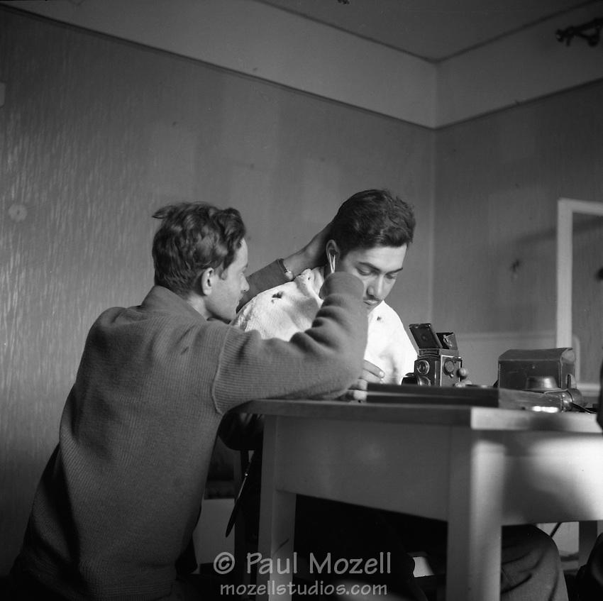 Clyde Smith gives photographer Ray Fisher a haircut while he tends to his Rolleicord camera.