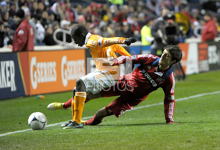 Chicago midfielder Alvaro Fernandez (4) attempts to slide tackle the ball away from Houston defender Corey Ashe (26).  The Houston Dynamo defeated the Chicago Fire 2-1 in the Eastern Conference play-in game for the MLS Playoffs at Toyota Park in Bridgeview, IL on October 31, 2012.