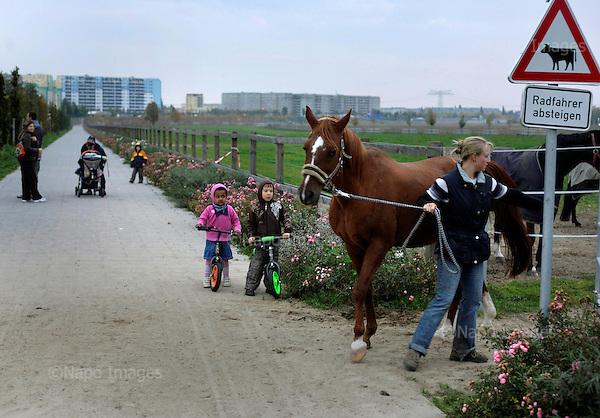 BERLIN, NIEMCY, 12/2008:.Dzieci przygladaja sie oniowi wyproweadzanemu z gruntow stajni w Rudow..Dwie dzielnice Berlina; Rudow, znajdujace sie w bylym Berlinie Zachodnim, oraz Treptow, po wschodniej stronie, byly przez lata rozdzielone murem berlinskim. Gdy mur runal, zostaly on z powrotem zjednoczone az do momentU, gdy miedzy nimi wyrosla nowa bariera - autostrada zbudowana wzdluz pasa ziemi niczyjej na ktorej stal mur.  .Fot: Piotr Malecki / Napo Images..Multiethnic children watch the horse by the stables in Rudow, west side of the former Berlin Wall.  East-side housing estate is visible in the background..Two Berlin neighbourhoods; Rudow, on the western side and Treptow in the East, used to be divided by the infamous Berlin Wall until 1989. Now they both are a part of the same Germany, although quite recently they have been divided again, by a new motorway built along the no-man's land of the wall. .Berlin - Rudow, December 2008.(Photo by Piotr Malecki / Napo Images) ..Berlin, Germany, November 2008.(Photo by Piotr Malecki / Napo Images)