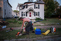 Work crew cleans up after removing a tree from a damaged home in Westerville, Ohio. The house, one of many damaged in a violent storm that felled trees and power lines leaving as many as 1 million people without power in Ohio, was declared a loss by the insurance adjuster.