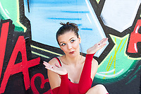 Female Model wearing red Tricot sitting in front of a colorful grafiti wall, making facial expressions during a break in an outdoor photoshoot.