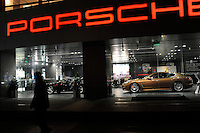 A passer-by walks pass the Porsche shop in central Shanghai. Imports of vehicles into China are expected to climb 20 percent to 420,000 units this year. Car makers, including Ferrari and Porsche, have accelerated new product launches....