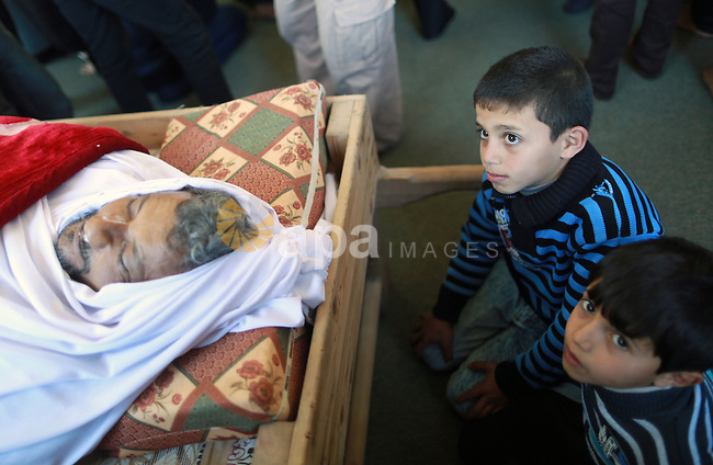 Palestinian boys look at the body of 48-year-old Yussef al-Buhairi during his funeral at a mosque in the al-Maghazi refugee camp, located in in the centre of the Gaza Strip, on December 28, 2015. Buhairi who was wounded at the Gaza border during clashes with the Israeli army the previous week died early on December 27 from his injuries, the Gaza health ministry said. Photo by Yasser Qudih