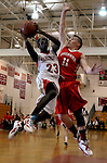 Manchester 23, Christian Walker goes up for the basket blocked by Greenwich 11, Alex McMurray,  in the second half of Tuesday's game at Manchester High School. (Jim Michaud/Journal Inquirer).