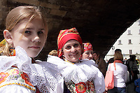 Headshot of women at the ride of Kings, dressed in traditional Moravian Costumes.<br /> <br /> Twelve-year-old Frantisek Libosvar dressed as a girl and with a rose in his mouth leads the royal procession during Ride of the Kings as part of Navalis Celebrations on May 15, 2015 in Prague, Czech Republic. The Navalis Saint John's celebrations take place to commemorate Czech saint and Prague native, Saint John of Nepomuk, patron of all people of the water. <br /> <br /> <br /> The Ride of the Kings takes place during the spring, as a part of the Pentecost traditions . A group of young men ride through a Prague in a ceremonial procession. The ride is headed by chanters, followed by pageboys with unsheathed sabres who guard the King &ndash; a young boy with his face partially covered, holding a rose in his mouth &ndash; and the rest of the royal cavalcade. The King and pageboys are dressed in women&rsquo;s ceremonial costumes, while the other riders are dressed as men. The entourage rides on decorated horses, stopping to chant short rhymes that comment humorously on the character and conduct of spectators. The chanters receive donations for their performance, placed either in a money box or directly into the riders&rsquo; boots. The King&rsquo;s retinue returns home after a few hours of riding, and celebrates in the evening at the house of the King with a small feast, music and dancing. The practices and responsibilities of the Ride of the Kings are transmitted from generation to generation. The traditional paper decorations for the horses and the ceremonial costumes, in particular, are made by women and girls familiar with the processes, colour patterns and shapes specific to each village.