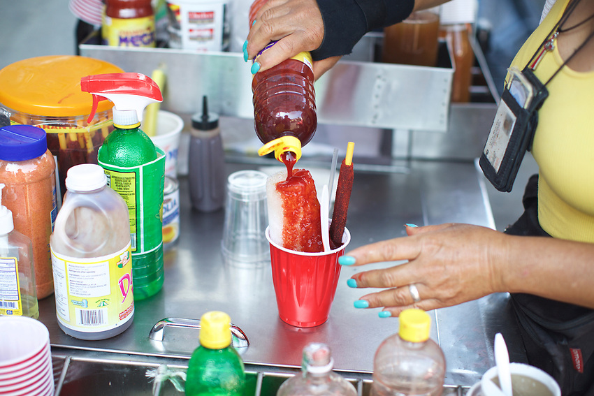 BROOKLYN, NY - July 25, 2015: A stand selling spicy, sweet chamoyadas on 5th Avenue served as a sweets break during the Taco Crawl through Sunset Park. Carmen, the owner, is Dominican and discovered the summer ice treat on a trip to Mexico and decided to start a business selling them to her Mexican neighbors.<br /> <br /> Credit: Clay Williams.<br /> <br /> &copy; Clay Williams / http://claywilliamsphoto.com