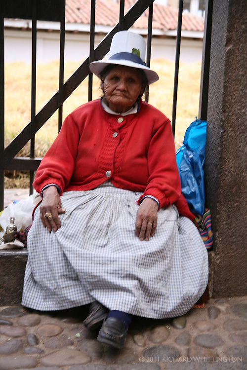 A Peruvian woman sitting on the sidewalk in Cuzco.
