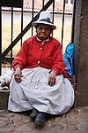 A Peruvian woman sitting on the sidewalk in Cuzco.